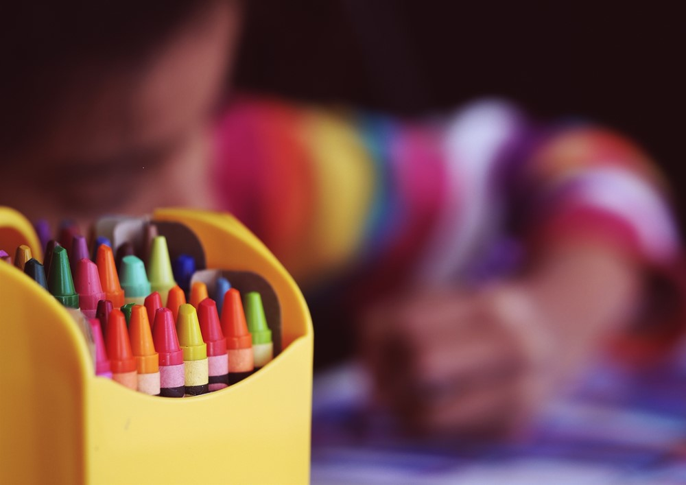 Crayons with student coloring in the backround